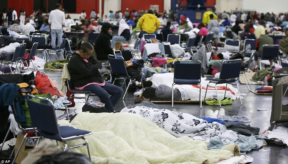 A woman naps on a chair while others sleep on the ground at the expansive shelter where hundreds are taking cover