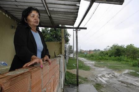 Antônia Maria Barbosa na porta de sua casa, na Rua João Mateus: só 20 metros da via foram asfaltados