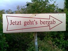 Schild mit einem Pfeil, auf dem steht: Jetzt geht's bergab