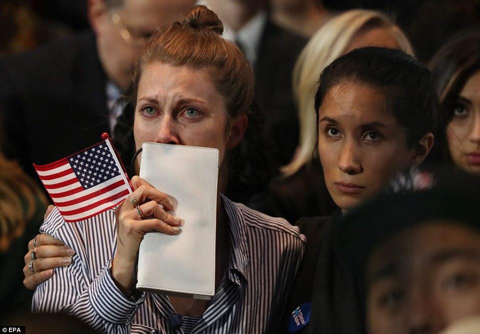 As pessoas na multidão em 2016 evento US presidencial da noite da eleição de Hillary Clinton assistir em lágrimas como resultados vêm em uma grande tela no Centro de Convenções Javits