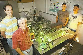 O físico Paulo Nussenzveig (à frente) e colegas em seu laboratório na USP; experimento traz base da internet no futuro