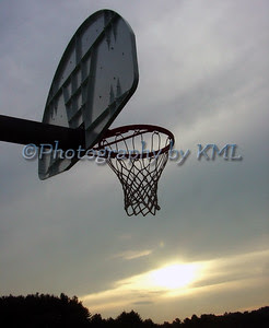 a basketball hoop against a setting sun