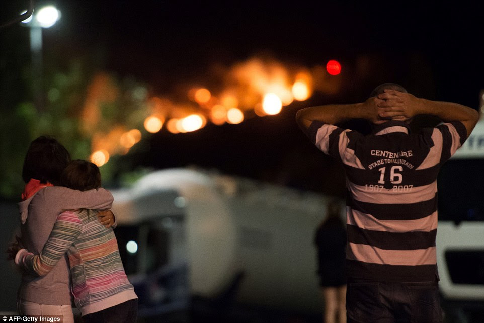 Um homem prende a cabeça entre as mãos e uma mulher abraça sua filha como eles olhar para os fogos na noite passada