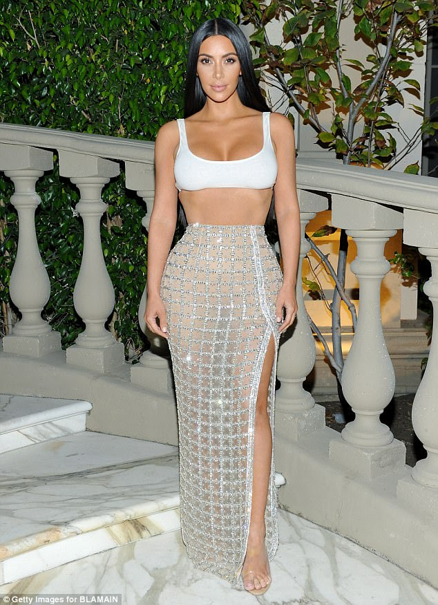 Glittering glamour: Kim Kardashian showed off her famous hourglass figure in a revealing embellished slit skirt with a white crop top