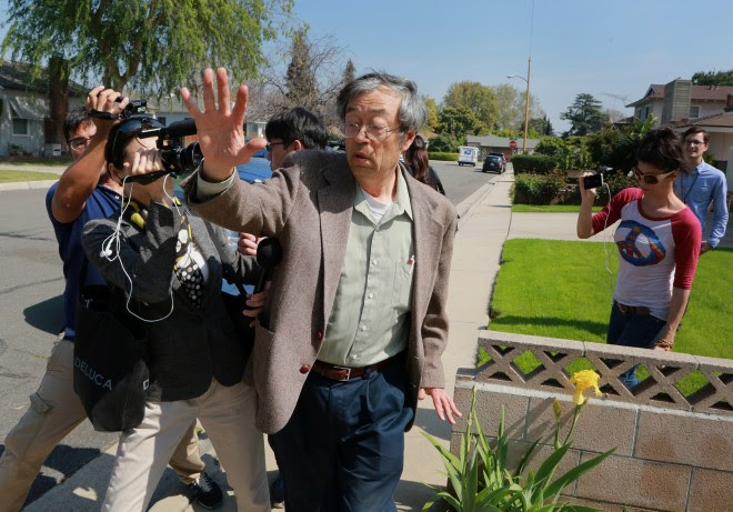Dorian S. Nakamoto,  exits his home surrounded by members of the media in Temple City, California, U.S., on Thursday, March 6, 2014. Photographer: Jonathan Alcorn/Bloomberg via Getty Images