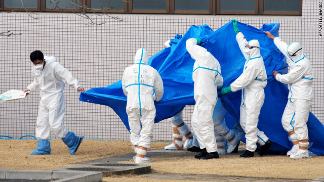 Military officers on Friday hold a blue sheet over people exposed to high levels of radiation at Japan's Fukushima Daiichi plant. AFP/Getty Images, via CNN, used w/o permission