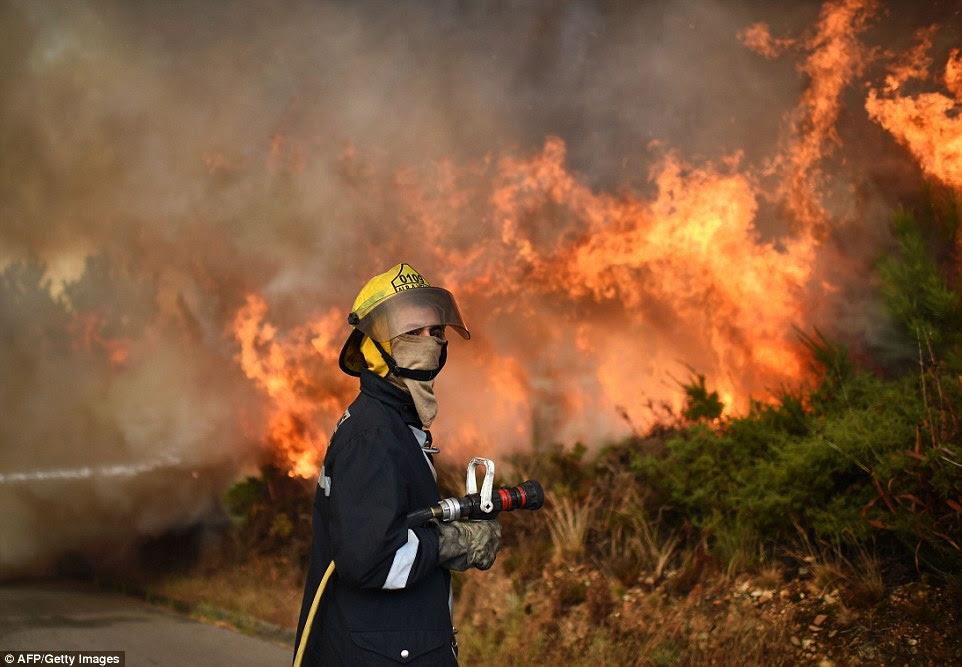 Perto deste bombeiro Português espera seu mangueira para ser conectado como um grande fogo arde fora de controle atrás dele.  Houve 100 incêndios separados em Portugal continental, bem como vários na ilha da Madeira