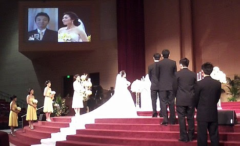 Skype wedding: Bride Helen Oh stands alone at the altar as her husband-to-be Samuel Kim watches her from his isolation ward on the jumbo-sized screen
