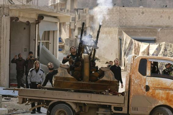 Free Syrian Army fighters fire an anti-aircraft weapon towards forces loyal to Syria's President Bashar al-Assad in the Handarat area, north of Aleppo November 30, 2014 .REUTERS-Hosam Katan