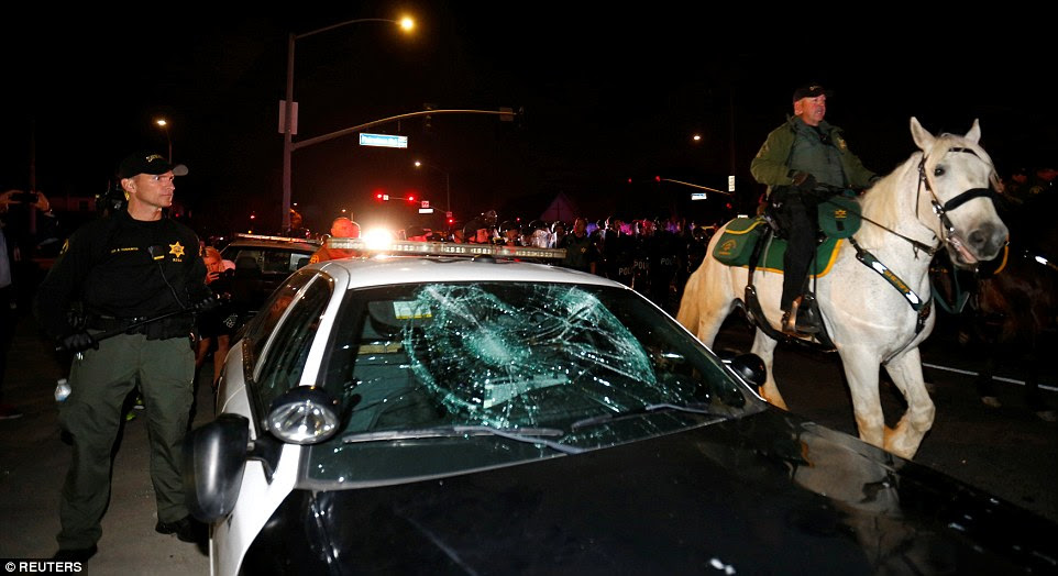One group of protesters was filmed trying to flip over a police car and arrests have been made outside outside the Pacific Amphitheater in Costa Mesa. A patrol car with a smashed window is pictured above