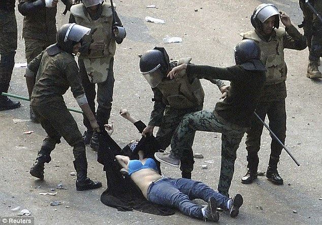 Brutal: Egyptian army soldiers drag this woman on the ground and kick her in the chest