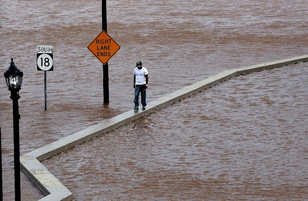 A man walks on top of a wall next  to a flooded highway in New Brunswick, N.J.,  Aug. 28, 2011, as heavy rains left by Hurricane Irene are causing inland flooding of rivers and streams.  Flood waters