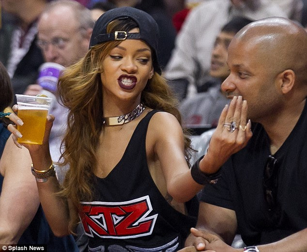 Handsy: Rihanna flirted with a male friend when she went to the basketball on Sunday night