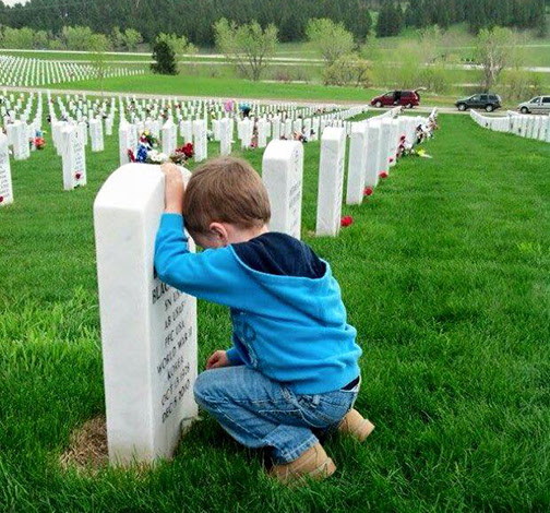 [Photo of a small boy kneeling in a military cemetery]