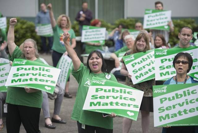 Kellie Klimcazk (left), a coder with the Labor and Industries' International Classification of Diseases (ICD) unit from Bonney Lake, and Diosy Page (center), an office assistant in L&I's bill processing department from Lacey, cheer during a rally for the Washington state employees union, AFSCME, at the Labor and Industries Building in Tumwater on Tuesday, June 21, 2016. Klimcazk has worked for the State of Washington for 15 years, Page for 28 years.
