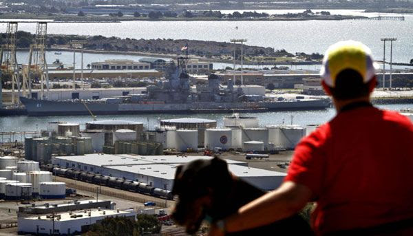 A Bay Area resident views the USS Iowa from an overlook.