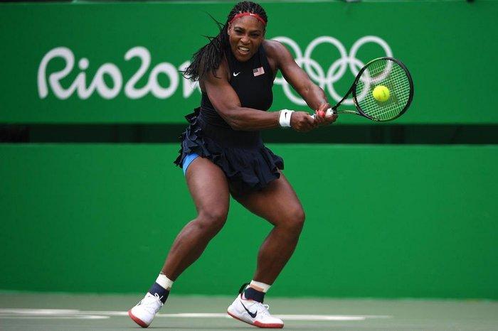 #DescriçãoDaImagem: mulher preta possui cabelo preso e veste top e saia pretos, tênis branco e raquete na mão rebatendo uma bola de tênis. Foto: Roberto Schmidit/AFP.