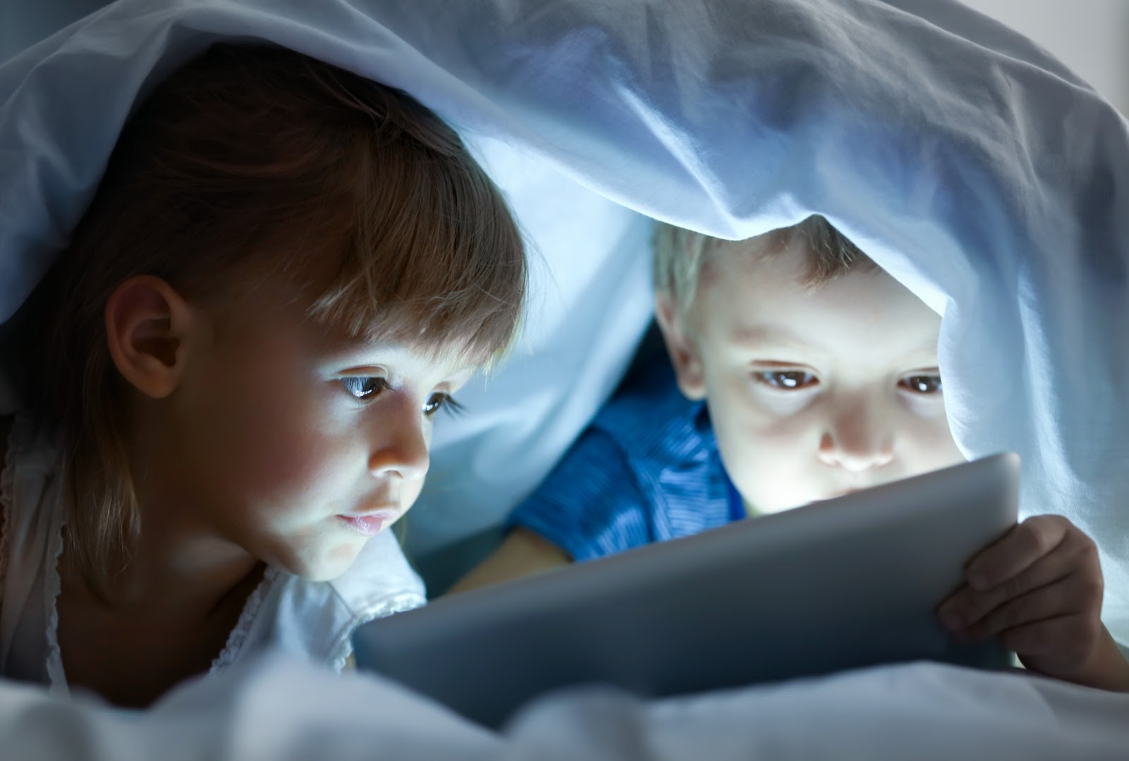 Young boy and girl under the covers  looking at an ipad screen