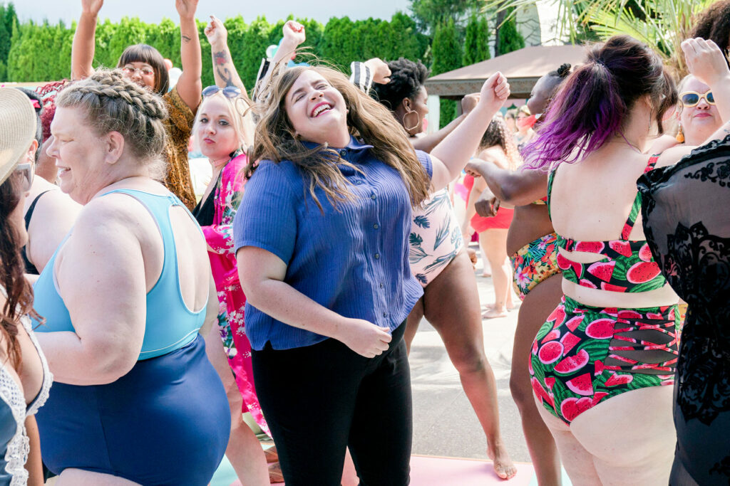 Annie in Shrill. Image: Annie dances in a crowd of people at the pool party. Annie is wearing a purple collared button up over black skinny jeans. Around her, people dance in a variety of colorful swimsuits.