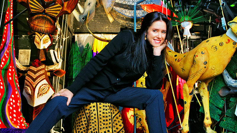 A promotional image of Julie Taymor, a slim white woman in her 60s with long black hair. She is sitting on a stool covered with a yellow patterned cloth, her legs spread apart with her elbow propped on her knee, her hand supporting her chin. She is smiling at the camera. Behind her is an array of theatre props such as model animals, masks, and headdresses in all different colours.