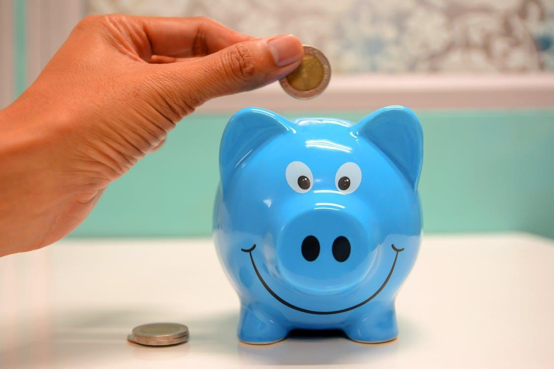 Person Putting Coin in a Piggy Bank