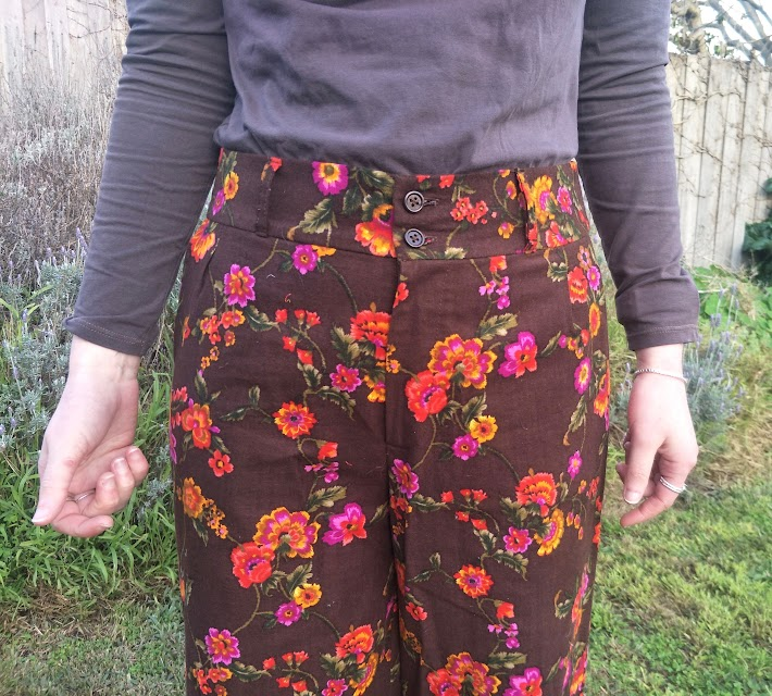 A close up of the waist area of brown pants with a pink and orange floral print. It is a good fit though the zip gapes/buckles slightly.
