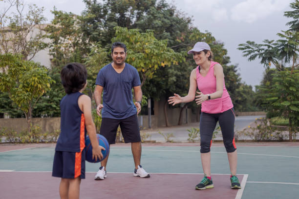 parents assisting their child in playing team sports