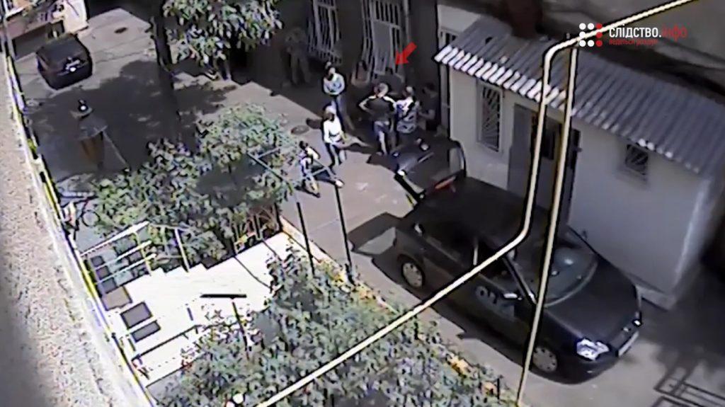 На заднем дворе больницы обвиняемый в особо тяжком преступлении встречается с компанией неизвестных.Там Пейкришвили тоже свободно гуляет без наручников.Мимо него проходят люди, некоторые - с детьми