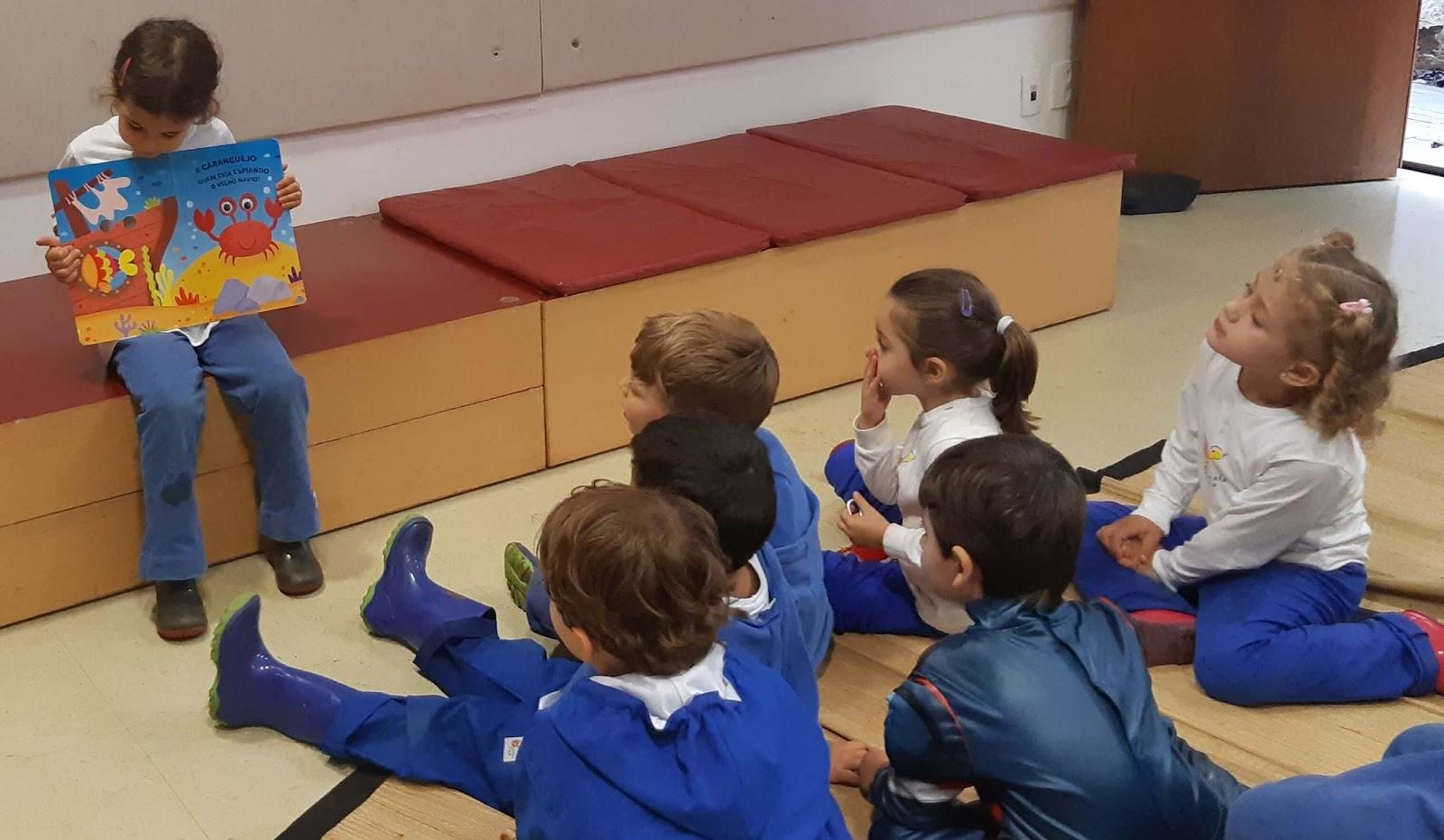 A imagem mostra uma criança mostrando um livro para um grupo de crianças.