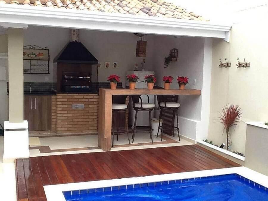 Área externa de casa com piscina, deck de madeira e espaço coberto com telhado de tijolos, churrasqueira de tijolinhos, bancada de madeira e paredes pintadas de branco.