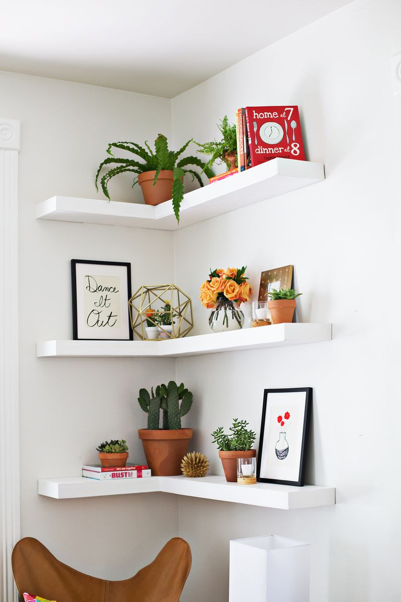 Corner shelving in a home with succulents, books and art prints as decor.