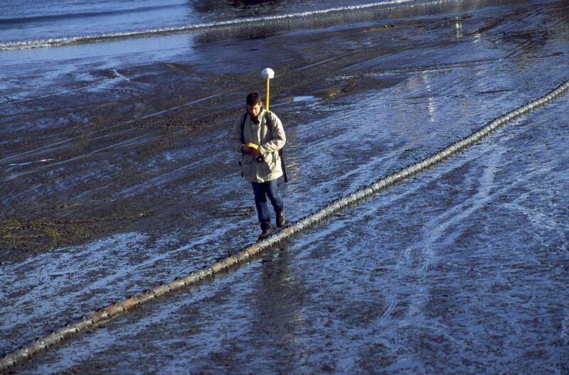 A man walks alongside a cable that runs across a damp, desolate field.