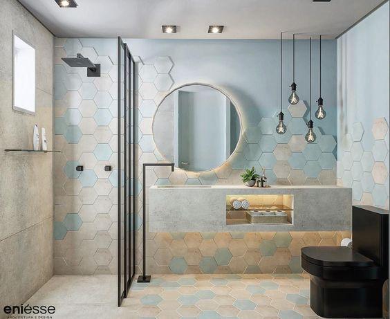 Banheiro com revestimento hexagonal no piso em tons de azul e dourado e meia parede com revestimento e demais área pintada de azul, luminárias pendentes, chuveiro, torneira e vaso sanitário pretos.