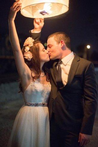 brides kissing each other under a wedding light