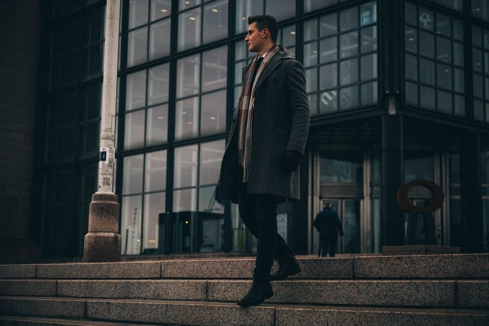 man wearing black trench coat walking on stair near building