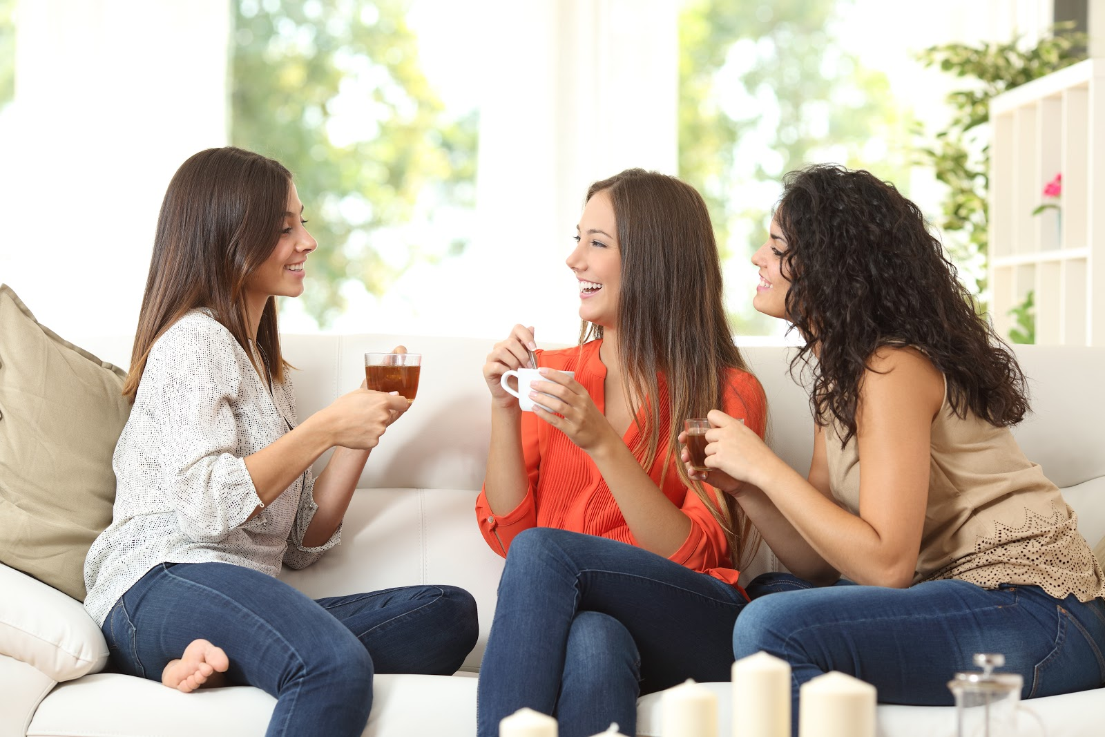Three co-homeowners sit on a sofa, drinking coffee and chatting.