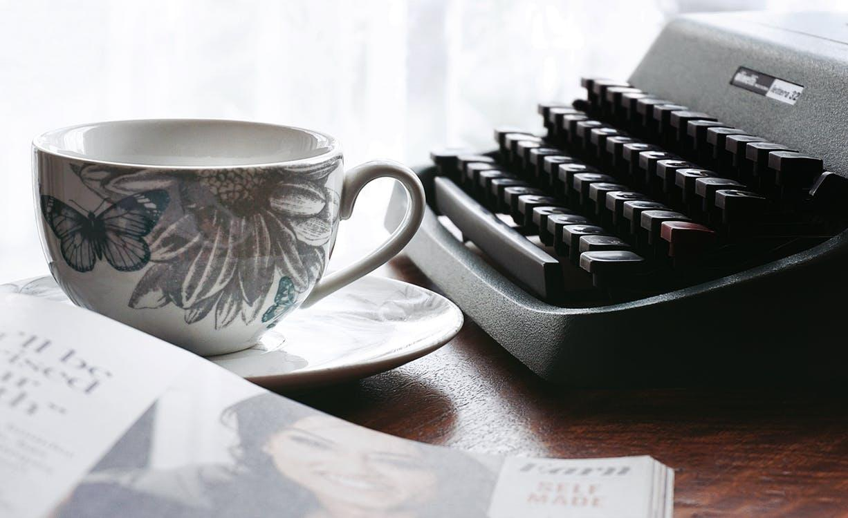 White and Gray Floral Ceramic Cup and Saucer Near Black Typewriter and Book - How to Develop a Daily Writing Habit
