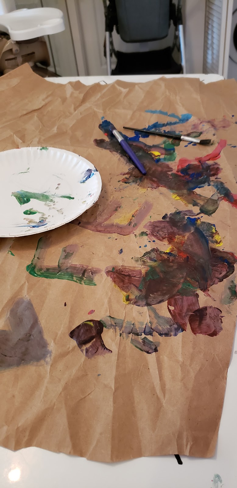 A toddler's painting on some brown paper. The letters F and E are present