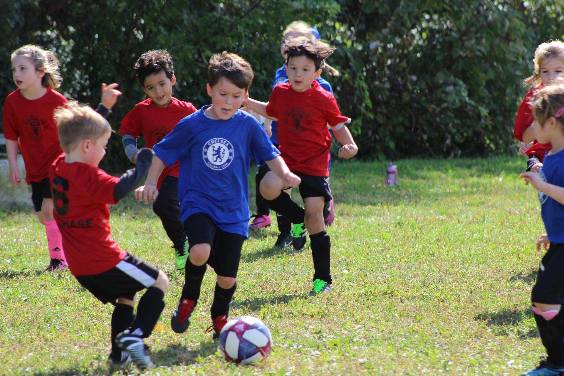 A group of kids playing football  Description automatically generated with medium confidence