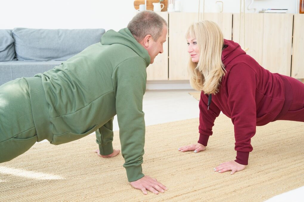 Older couple doing exercise together at home. How to start an at-home fitness routine.