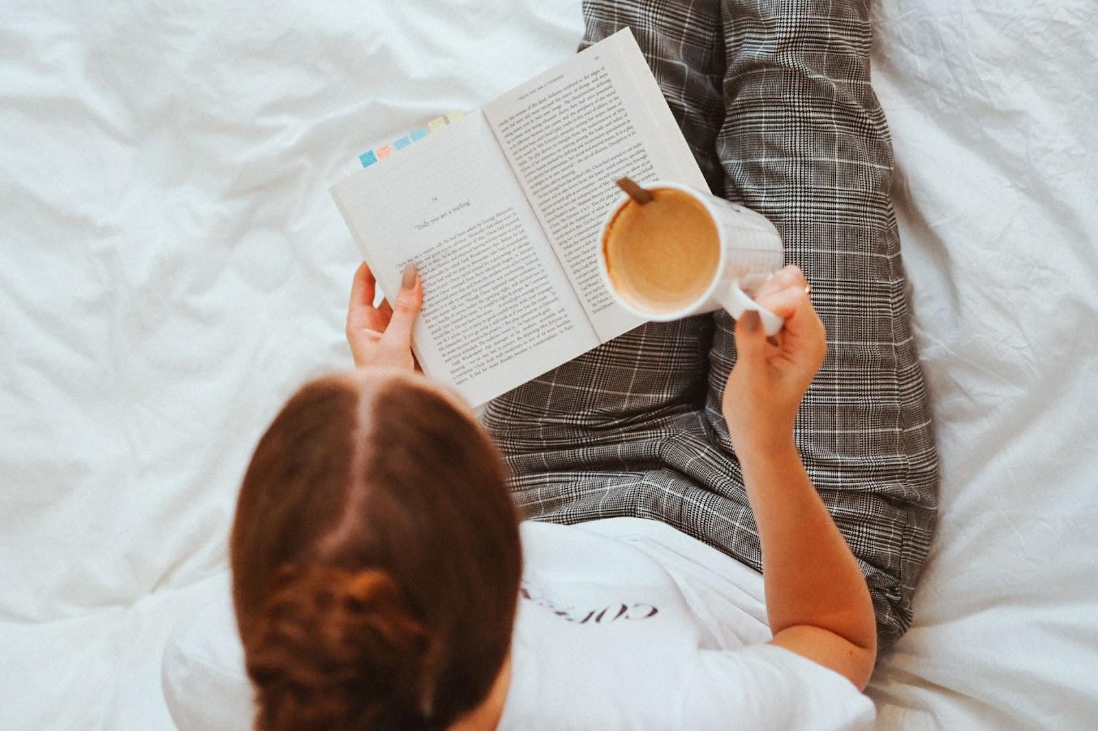 Menina sentada na cama lendo um livro
