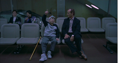 Bill Murray as Bob in Lost in Translation (2003). Bob is sitting in a waiting room, looking perplexed at the Japanese man with a walking stick sitting beside him, who points up at the sky.