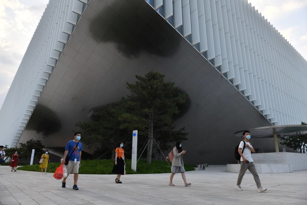 Staff walk out from the headquarters building of Tencent, the parent company of Chinese social surveillance system WeChat, in Beijing on August 7, 2020. The reason China blocks Signal is to hem Chinese netizens into using WeChat, where CCP surveillance and censorship are a part of everyday life.