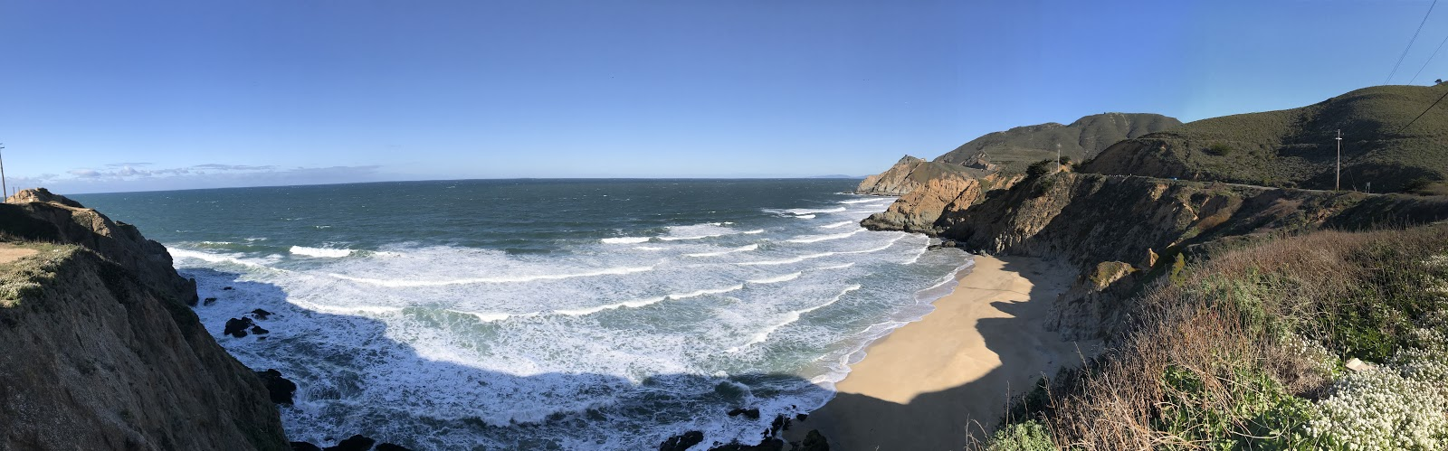 panoramic view beautiful secluded california sandy beach and wavy ocean surrounded by green hills on a clear day. See the beautiful coast of California during a california road trip