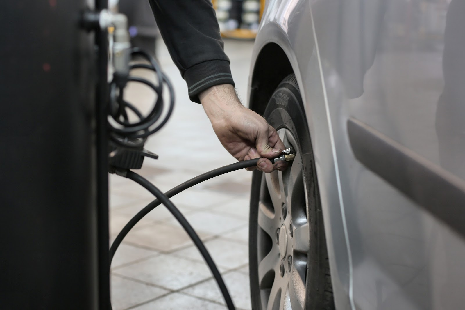 Homem calibrando pneu segurando mangueira com uma das mãos.