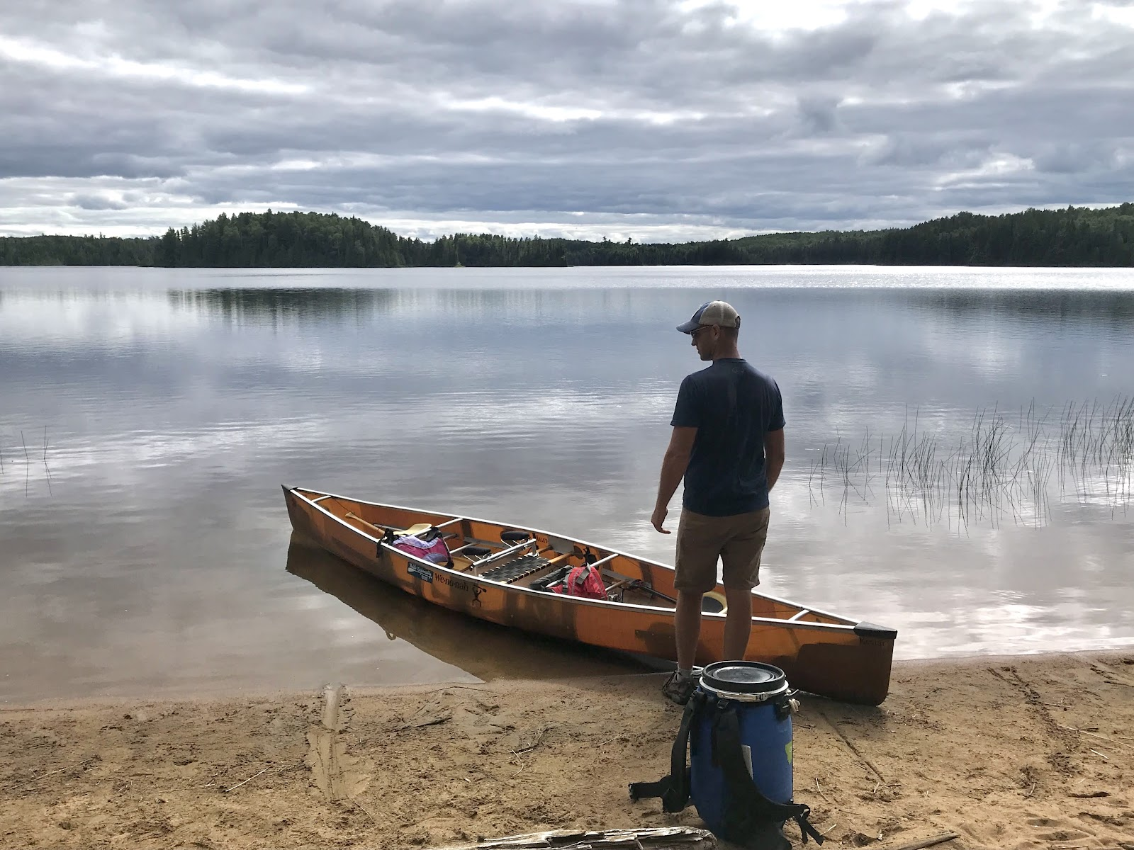 Nick standing next to the canoe in front of a lake. Blue barrel nearby.