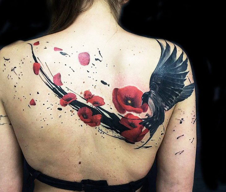 Tatuagem de corvo e flores nas costas de uma garota