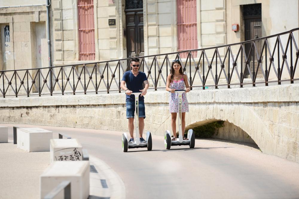 Homem e mulher testando veículo Segway PT em rua