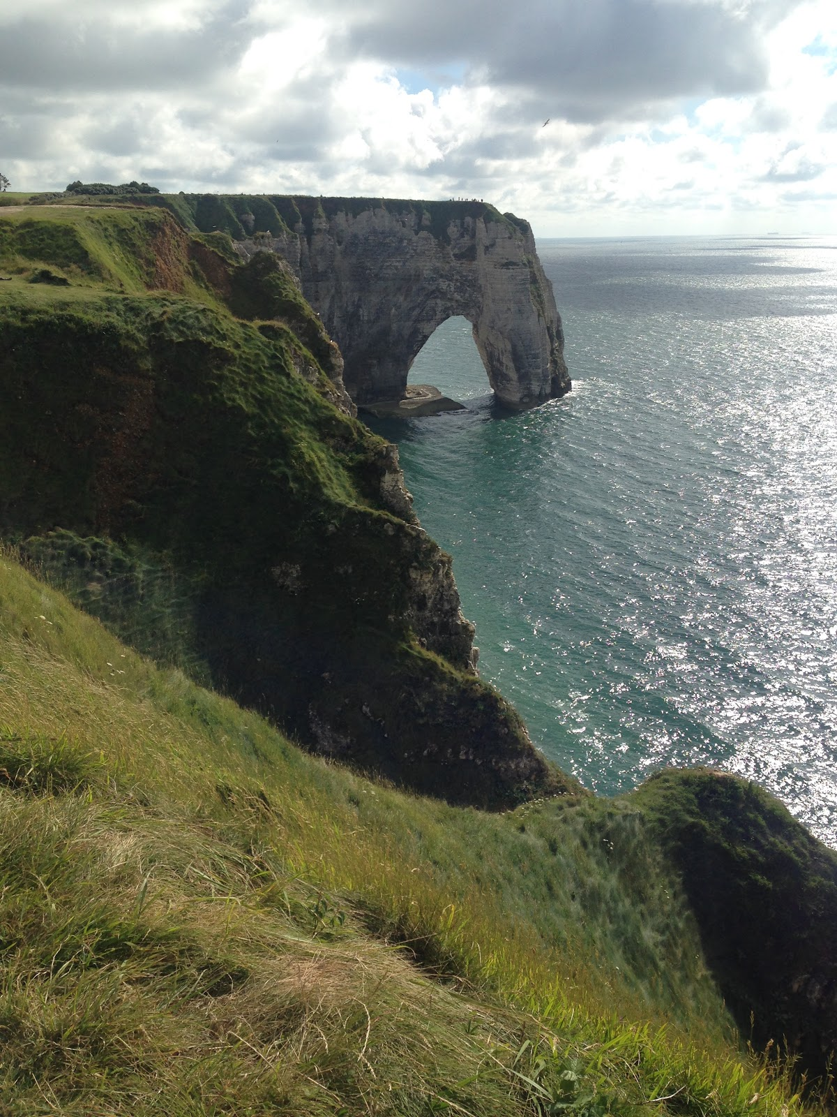 etretat france, dramatic coastline with large cliff. Calm ocean, green grass and sunny yet cloudy weather.