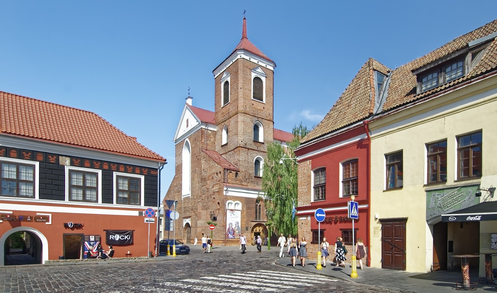 old town kaunas, traditional architecture and large brick church in the middle of the frame. tourists walking around on this sunny day in lithuania